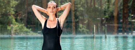 Photo pour Plan panoramique de belle femme sexy avec les mains sur la tête posant dans la piscine sur la station - image libre de droit