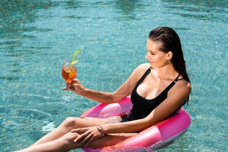Foto de Hermosa chica con cóctel en el anillo de natación en la piscina en el complejo - Imagen libre de derechos