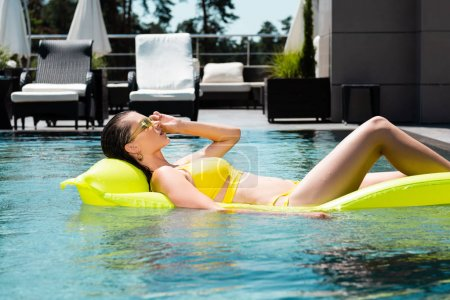 Photo for Beautiful girl swimming on inflatable mattress in pool on resort during daytime - Royalty Free Image