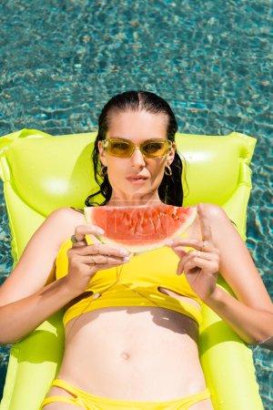 Photo pour Belle fille sur le matelas gonflable avec la pastèque dans la piscine sur la ressource - image libre de droit
