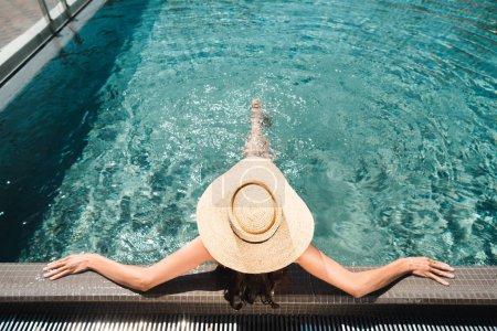 Photo pour Vue de dos sur la femme dans le chapeau de paille détendant dans la piscine - image libre de droit