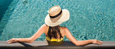 Photo for Back view on woman in straw hat relaxing in swimming  pool, panoramic shot - Royalty Free Image