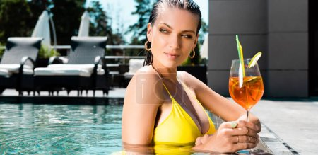 Photo for Panoramic shot  of beautiful girl in swimming suit in swimming pool with cocktail on resort - Royalty Free Image