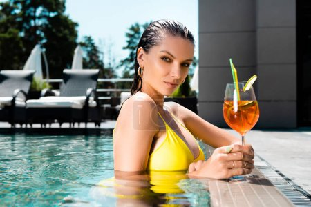 Photo pour Belle fille dans le maillot de bain avec le cocktail sur la ressource dans la piscine - image libre de droit