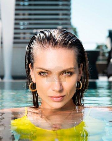Photo pour Belle femme regardant l'appareil-photo tout en posant dans la piscine - image libre de droit