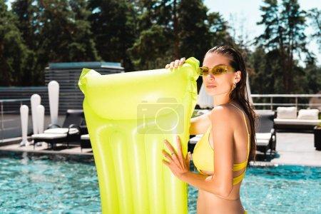 Foto de Hermosa chica en gafas de sol con colchón inflable cerca de la piscina en el complejo - Imagen libre de derechos