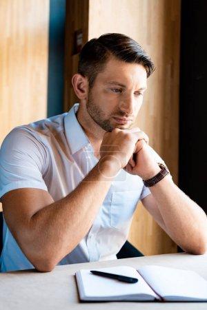 Foto de Hombre musculoso pensativo sentado con las manos apretadas en el café - Imagen libre de derechos