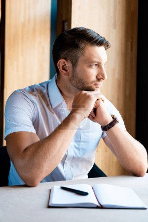 Photo for Pensive muscular man sitting with clenched hands in cafe - Royalty Free Image