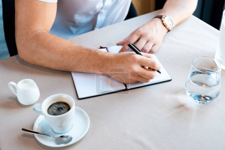 Photo for Partial view of man writing in textbook while sitting in cafe - Royalty Free Image