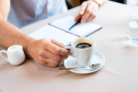 Photo for Partial view of man holding cup of coffee while sitting in cafe with textbook and pen - Royalty Free Image