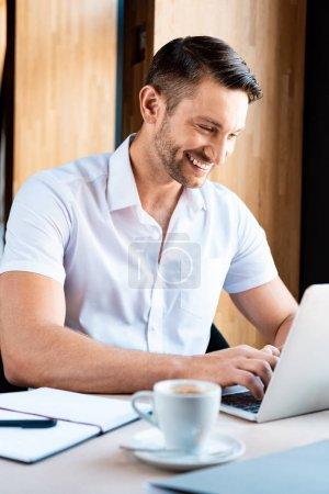 Photo pour Sourire freelance dactylographier sur clavier d'ordinateur portable dans le café - image libre de droit