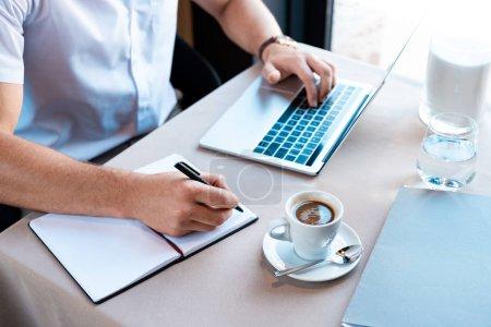 Photo pour Vue partielle de l'écriture freelance dans le manuel et dactylographier sur clavier d'ordinateur portable dans le café - image libre de droit