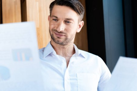 focused man looking at documents with gently smile in cafe