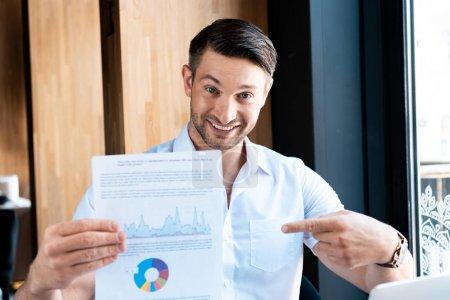 Photo pour Vue de face de l'homme souriant pointant du doigt le document avec le diagramme dans le café - image libre de droit