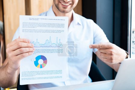 Photo for Cropped view of smiling man pointing with finger at document with diagram in cafe - Royalty Free Image