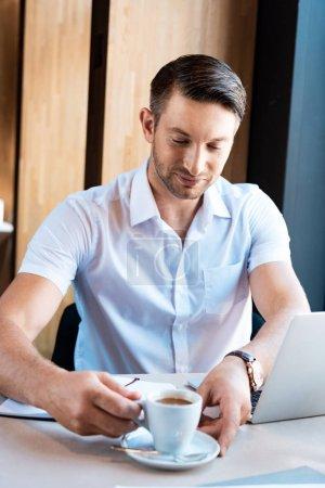 Photo pour Pigiste souriant tenant la soucoupe et la tasse de café tout en s'asseyant à la table avec l'ordinateur portatif dans le café - image libre de droit