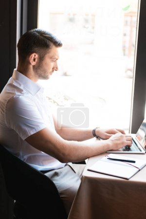 Photo for Side view of focused freelancer typing on laptop keyboard while sitting in cafe - Royalty Free Image