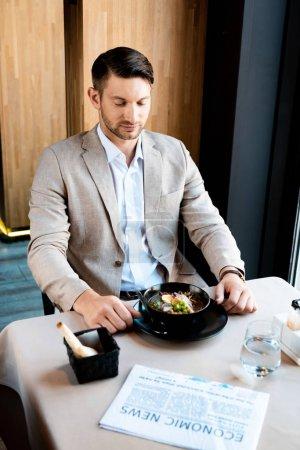 homme d'affaires assis à table avec de la nourriture, de l'eau et des journaux dans un café