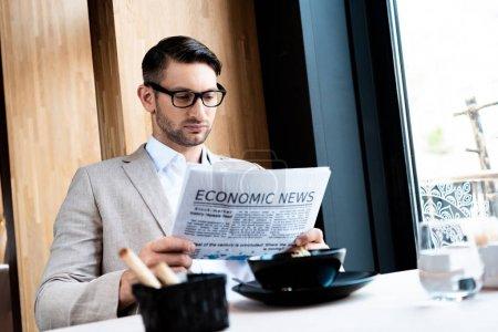 Photo pour Homme d'affaires concentré dans les lunettes de lecture journal dans le café - image libre de droit