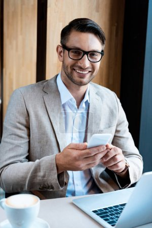 Photo for Smiling businessman in glasses holding smartphone while sitting at table with laptop in cafe - Royalty Free Image