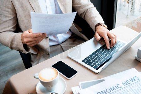 Photo pour Vue recadrée de l'homme d'affaires tenant le document et tapant sur le clavier de l'ordinateur portable dans le café - image libre de droit