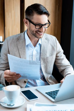 Photo for Smiling businessman in glasses holding document and typing on laptop keyboard in cafe - Royalty Free Image