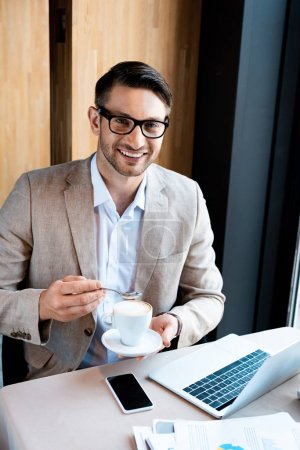 Photo for Smiling businessman in glasses holding cup of coffee while sitting at table with laptop in cafe - Royalty Free Image