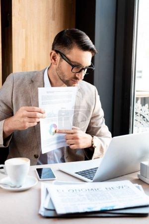Photo pour Homme d'affaires dans des glaces affichant le document à l'écran d'ordinateur portatif dans le café - image libre de droit
