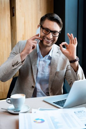 smiling businessman in glasses talking on smartphone and showing okay sign in cafe
