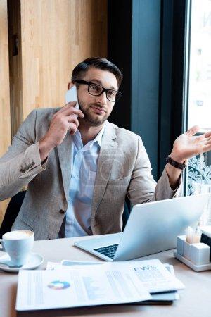 Photo pour Homme d'affaires en lunettes parlant sur smartphone devant un ordinateur portable dans un café - image libre de droit