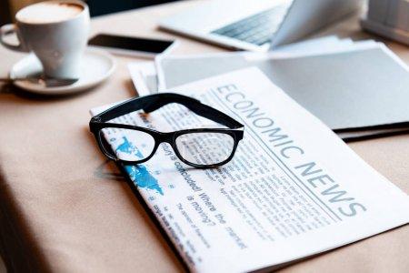 Photo pour Ordinateur portable et smartphone, tasse de café, documents, journal et verres sur la table dans le café - image libre de droit