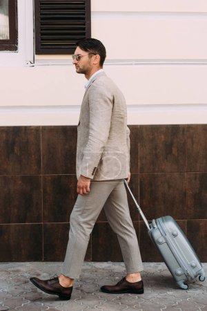 Photo pour Vue pleine longueur de l'homme d'affaires en lunettes de soleil tenant valise sur la rue - image libre de droit