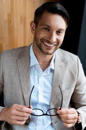 Photo for Smiling businessman holding glasses and looking at camera - Royalty Free Image
