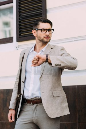 businessman in glasses and wristwatch looking away on street