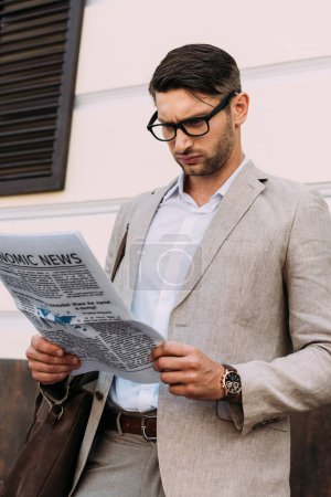focused businessman in glasses reading newspaper on street
