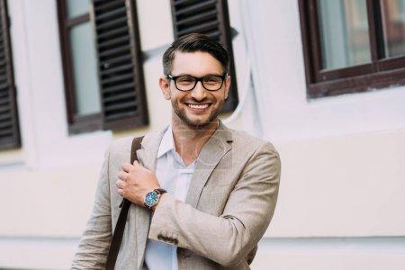 Photo pour Homme d'affaires de sourire dans des glaces et une montre-bracelet sur la rue - image libre de droit