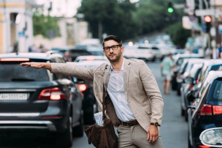 businessman in glasses with bag hitching ride on street