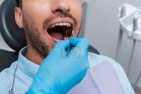 Photo pour Vue recadrée de dentiste retenant le miroir dentaire dans la bouche du patient barbu - image libre de droit