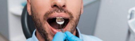 Photo pour Tir panoramique de dentiste retenant le miroir dentaire dans la bouche du patient barbu - image libre de droit