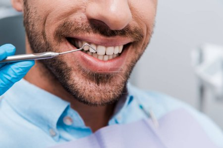 Photo for Cropped view of dentist holding dental instrument near cheerful man - Royalty Free Image