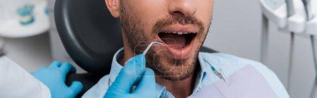 Photo pour Tir panoramique du dentiste retenant l'instrument dentaire près de l'homme - image libre de droit