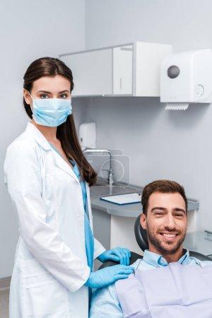 Photo pour Dentiste dans le masque médical et les gants de latex restant près du patient heureux - image libre de droit