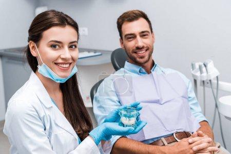 Photo pour Foyer sélectif de dentiste attrayant dans des gants en latex tenant le modèle de dents près du patient avec les mains serrées - image libre de droit