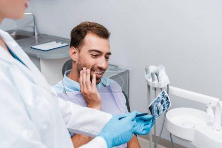 Photo pour Foyer sélectif de l'homme joyeux regardant la radiographie près du dentiste en manteau blanc - image libre de droit