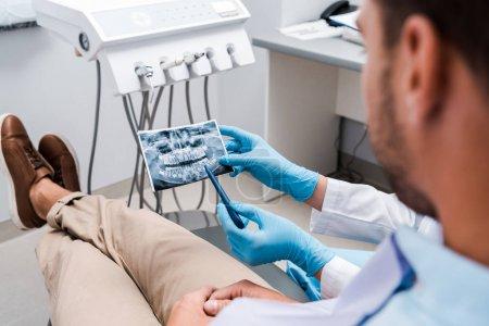 Photo pour Recadré de dentiste tenant un stylo près de la radiographie et patient en clinique - image libre de droit