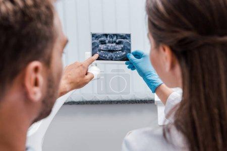 Photo pour Vue recadrée du dentiste tenant une radiographie près du patient pointant du doigt en clinique - image libre de droit