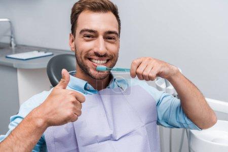 Photo pour Bel homme barbu affichant le pouce vers le haut tout en retenant la brosse à dents - image libre de droit