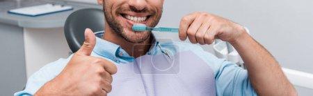 Photo pour Plan panoramique de l'homme barbu montrant pouce levé tout en tenant la brosse à dents - image libre de droit