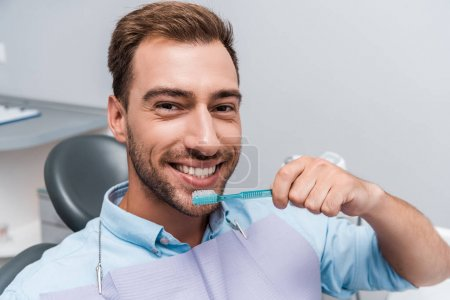 happy bearded man looking at camera and holding toothbrush