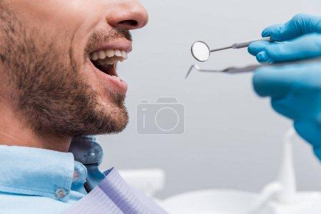 Photo pour Vue recadrée de femme dans des gants en latex retenant des instruments dentaires près du patient - image libre de droit
